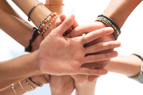 Closeup hands of a group of people. Low angle view of multiethnic friends stacking hands over each o